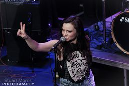 laura james makes a peace sign while performing on stage