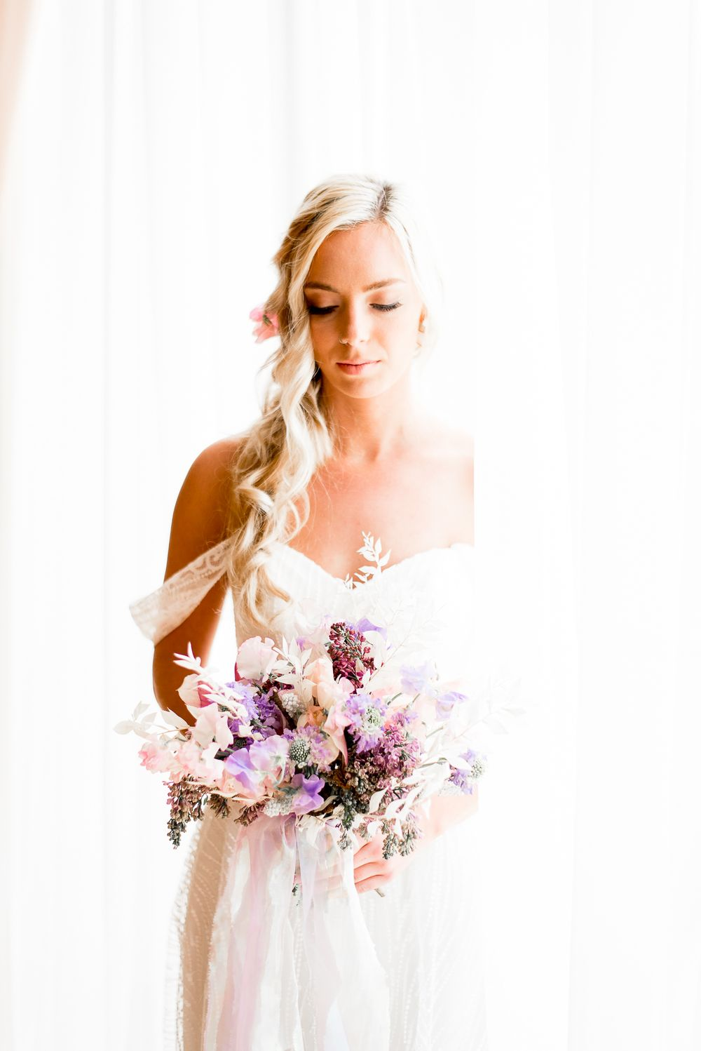 blonde bride with braided hair looking at her colorful purple and pink spring wedding bouquet