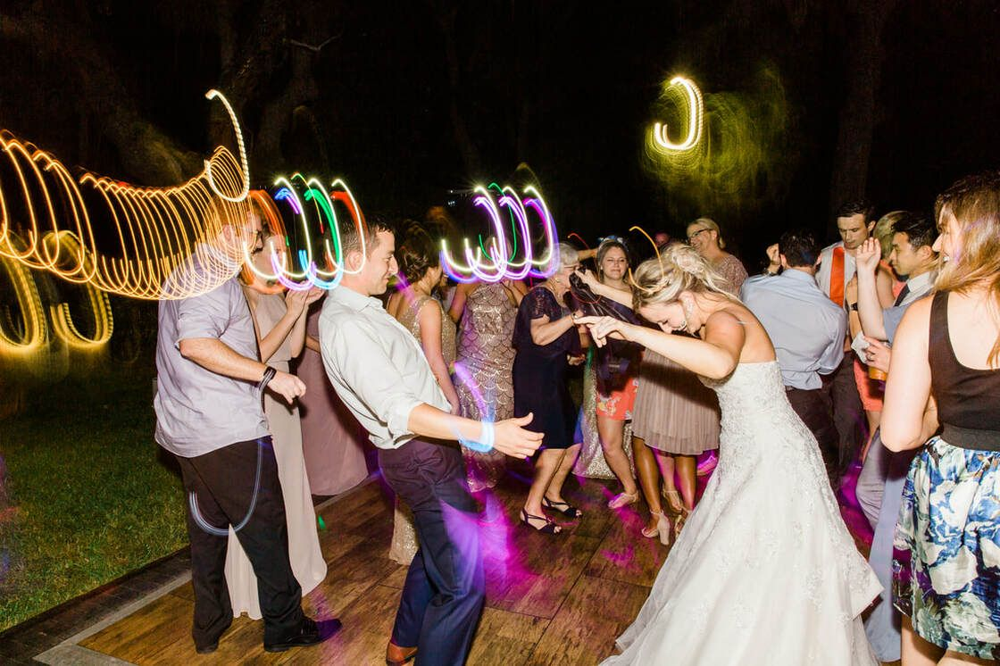 bride and groom dance during during outdoor wedding reception at captain's bluff in ssi