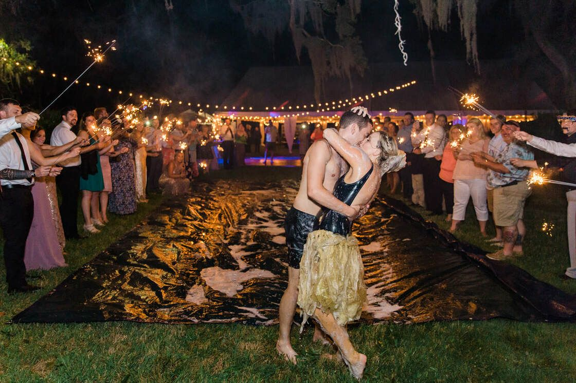 bride and groom kiss at the end of their slip-n-slide sparkler exit at caption's bluff in st simon's island