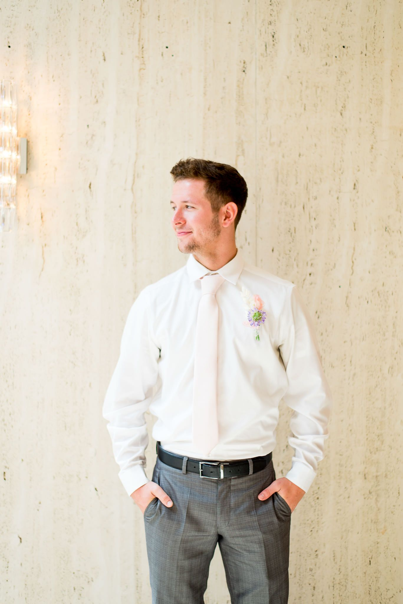 groom with blue eyes, light pink tie, and pink and purple boutonniere in front of marble wall at The Center Cincinnati