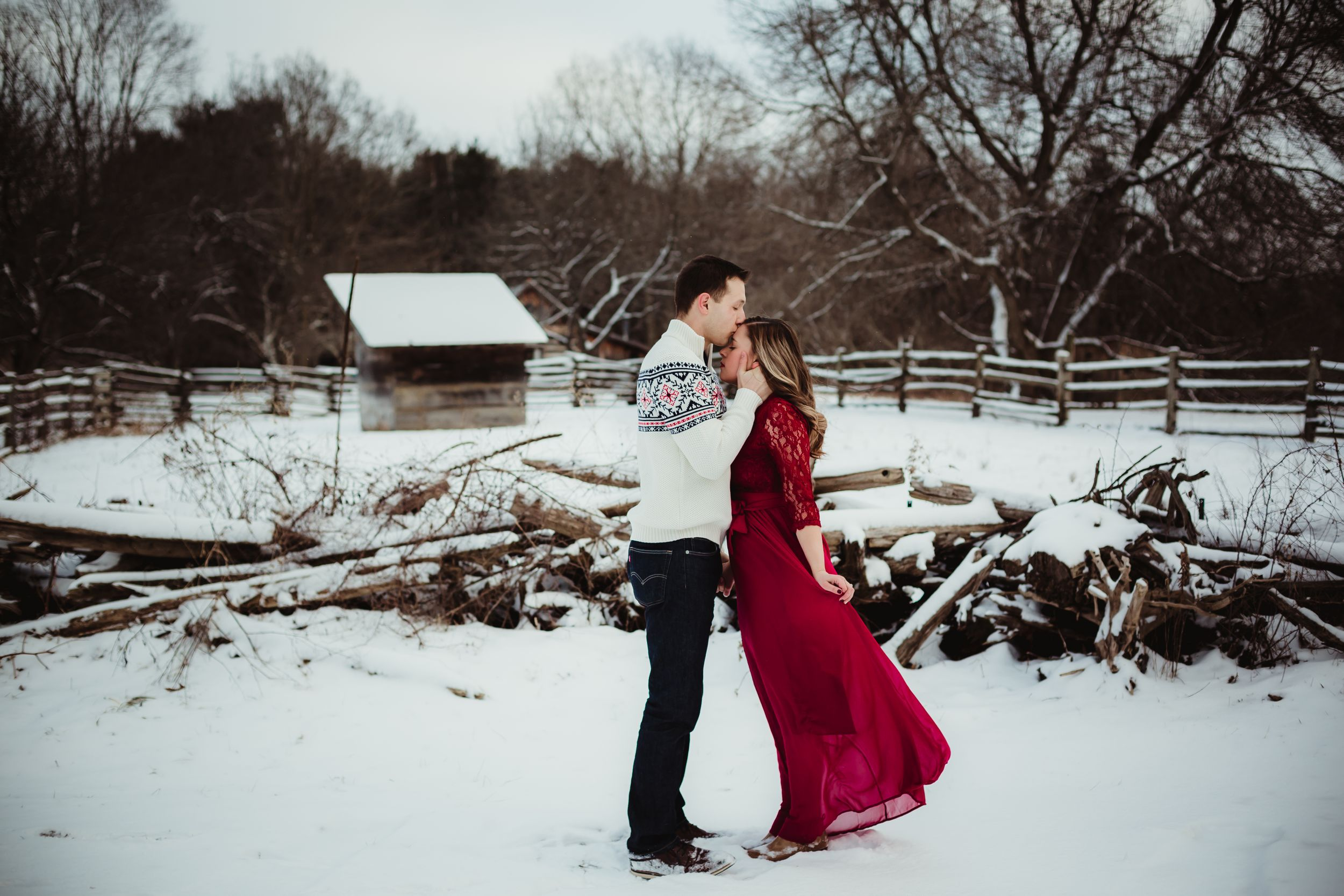 A man kissing a woman's forehead outside in the winter surrounded by snow. She is wearing a long red dress.