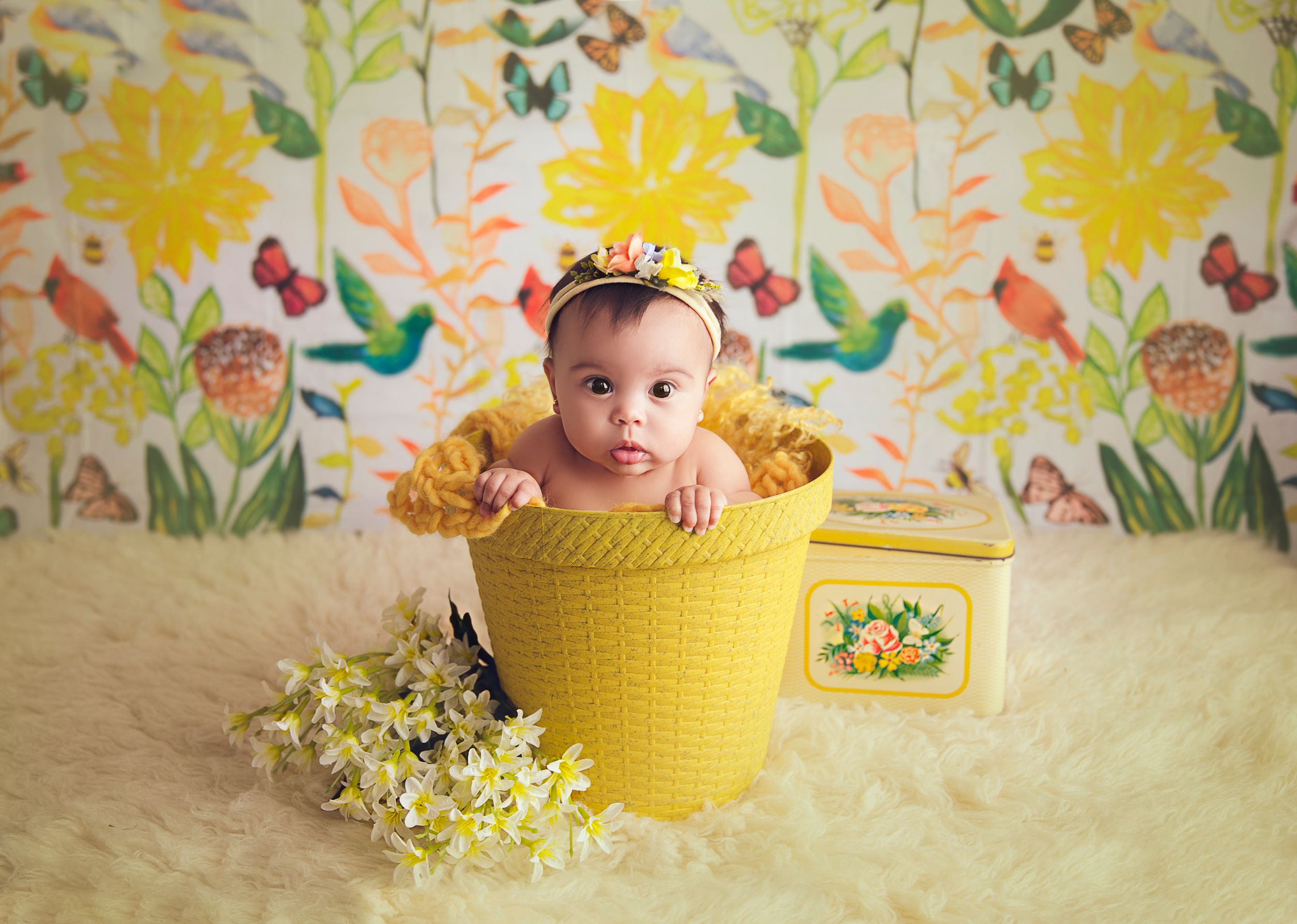baby girl in a yellow bucket floral backdrop