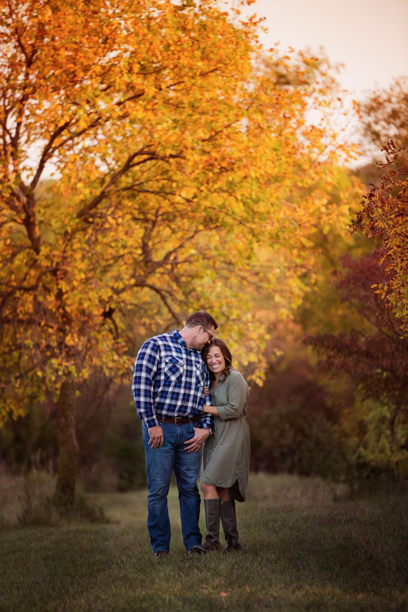 Couple laughing in front of fall leaves in Omaha, Nebraska