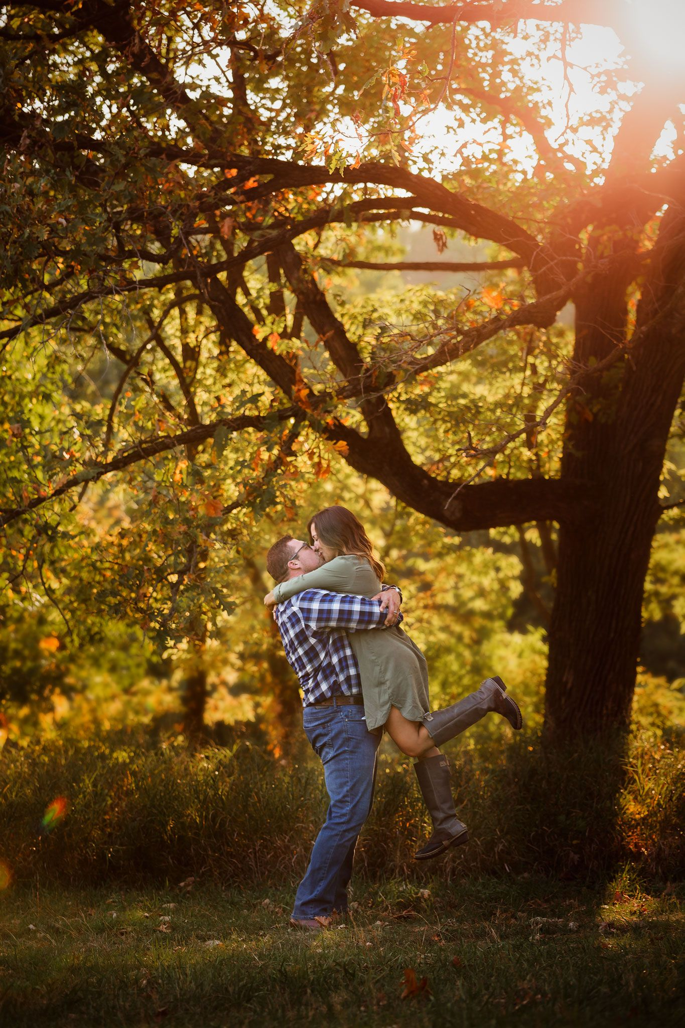 A couple posed for a photo under a sunlit tree in Omaha, Nebraska.