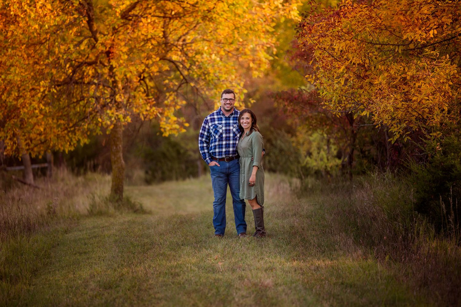 Couple standing in front of fall colored tree in Omaha, Nebraska