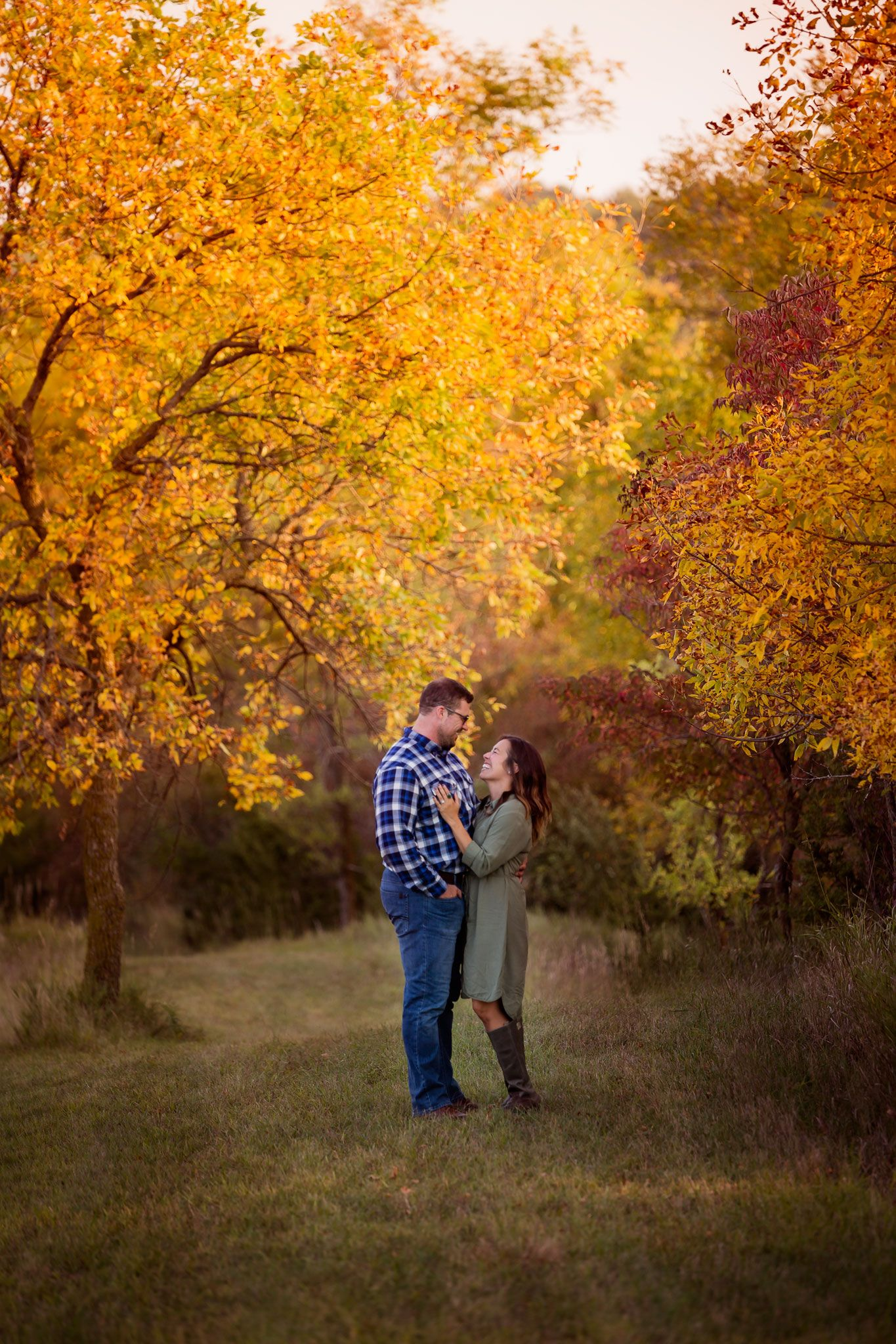 Omaha couple photographed under fall trees.