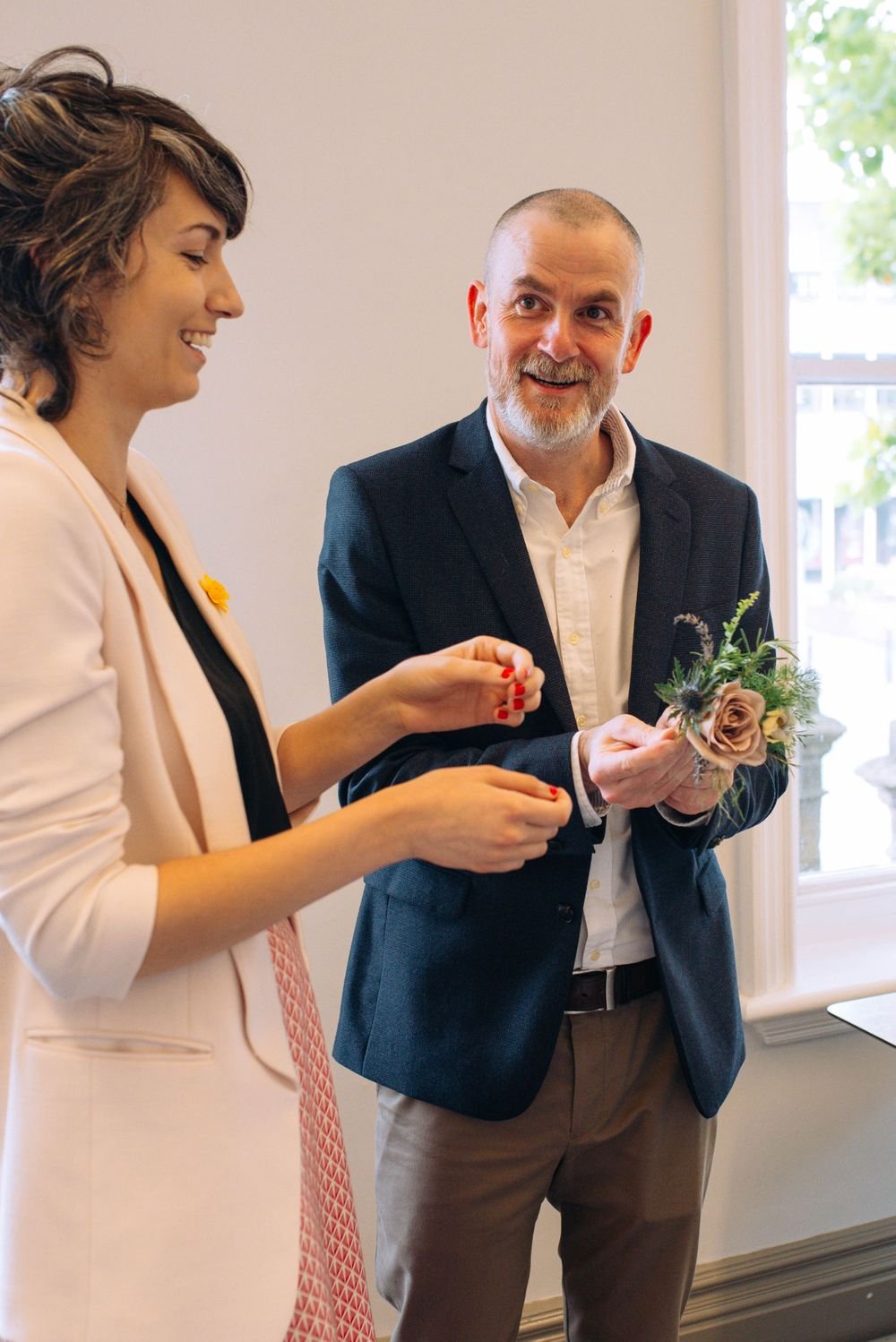 Frome Town Hall wedding by Zara Davis Photography, Gloucestershire putting on buttonholes