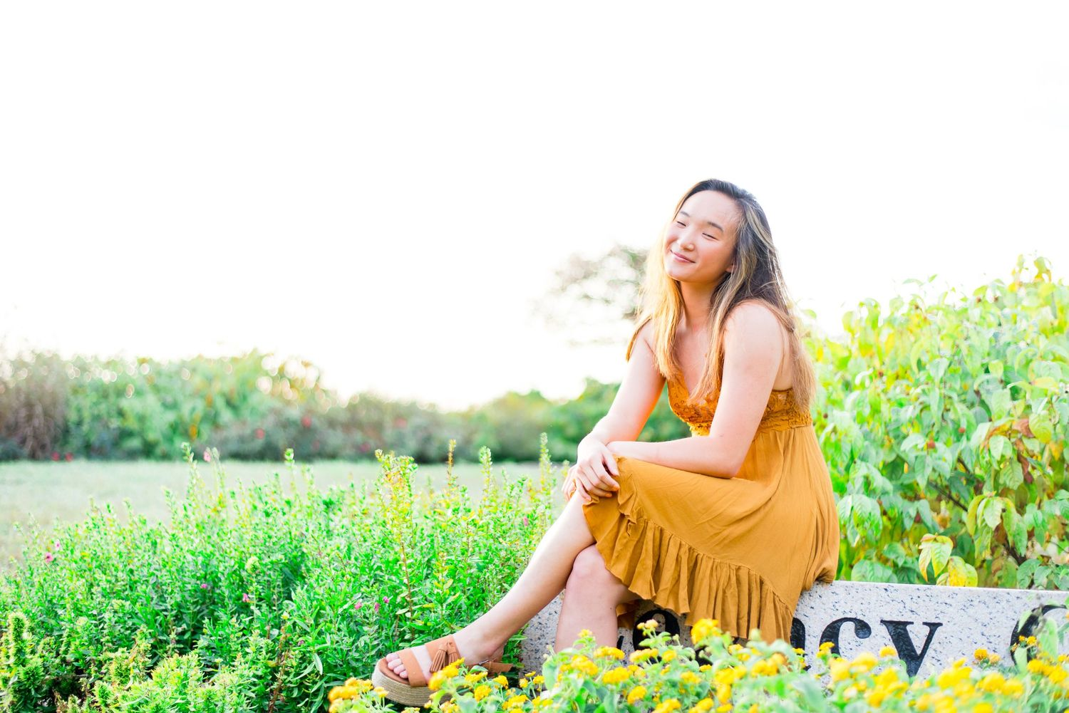 young woman sitting on a stone with legs crossed and smiling in a field of yellow flowers