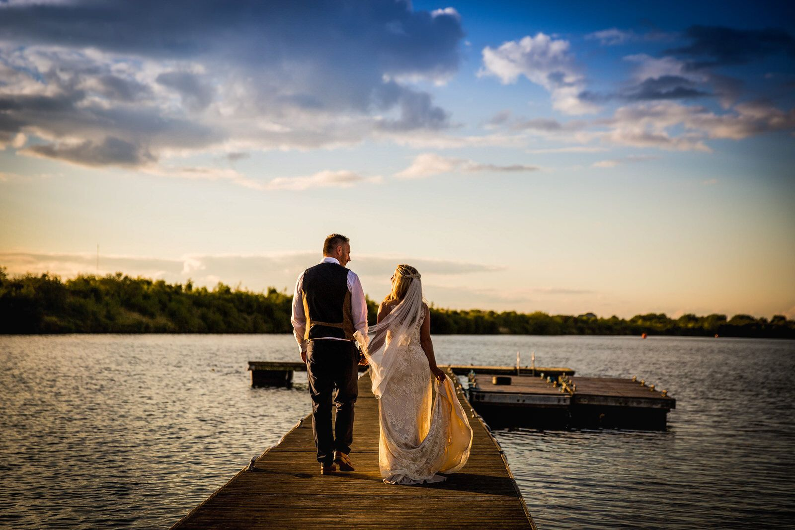 Bride & Groom walking into sunset along a jetty