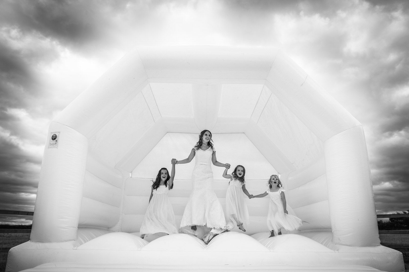 bride with bridesmaids on bouncy castle