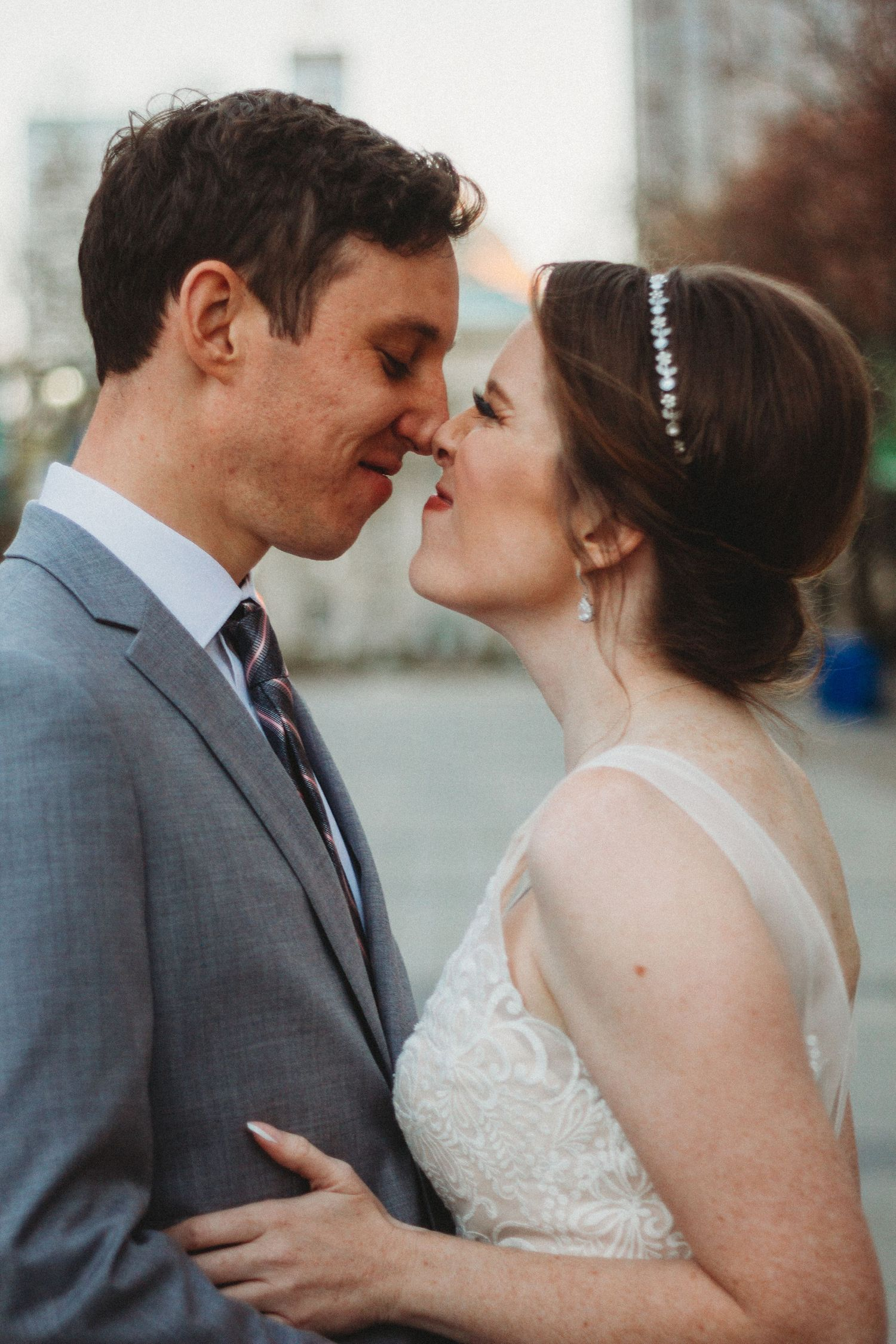 bride and groom touch noses while in downtown raleigh