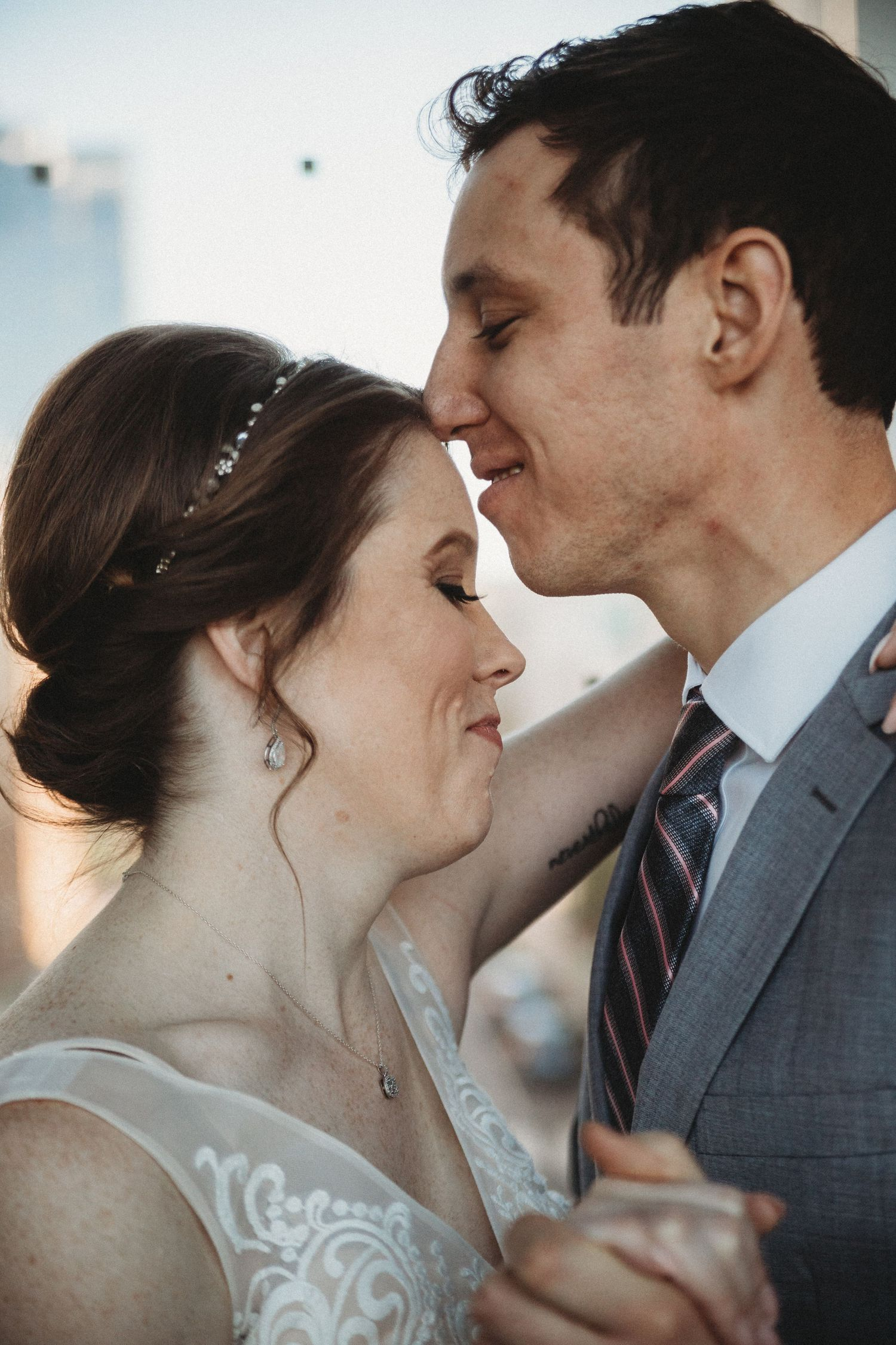 bride and groom nuzzle noses on skywalk