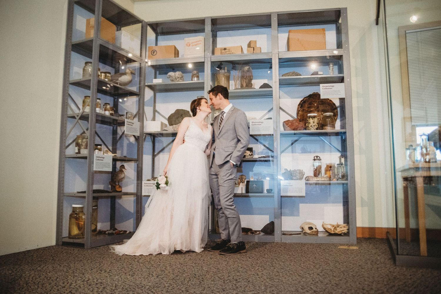 bride and groom kiss for a potrait in front of preserved biology