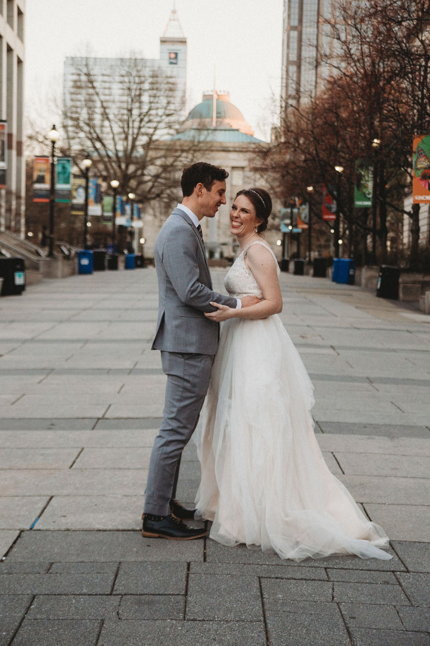 bride and groom laugh in pedestrian downtown walkway in raleigh