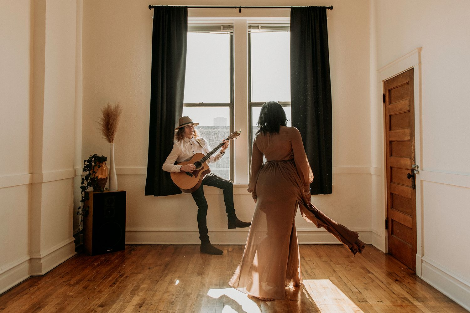 woman dancing with man playing guitar behind her during studio couples session