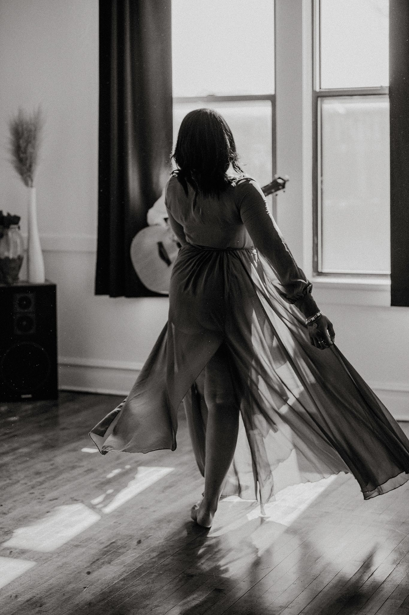 black and white image of woman dancing with her flowy dress facing her boyfriend playing guitar