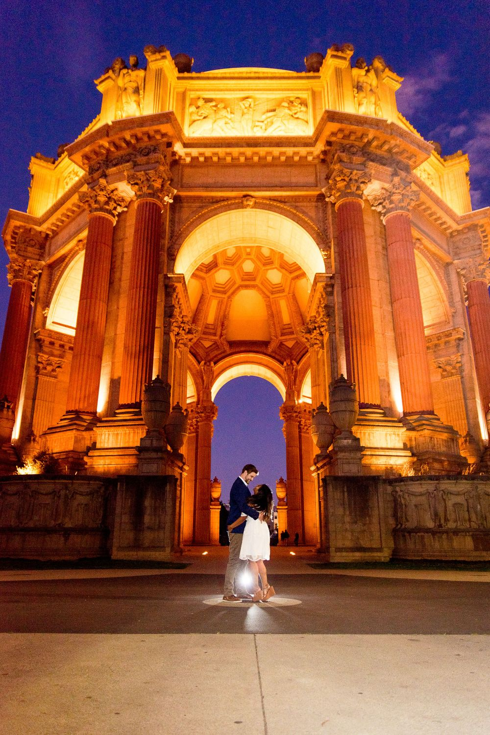 engaged girl in white dress and man in navy jacket and tan pants hugging at night in front of Palace of Fine Arts SF