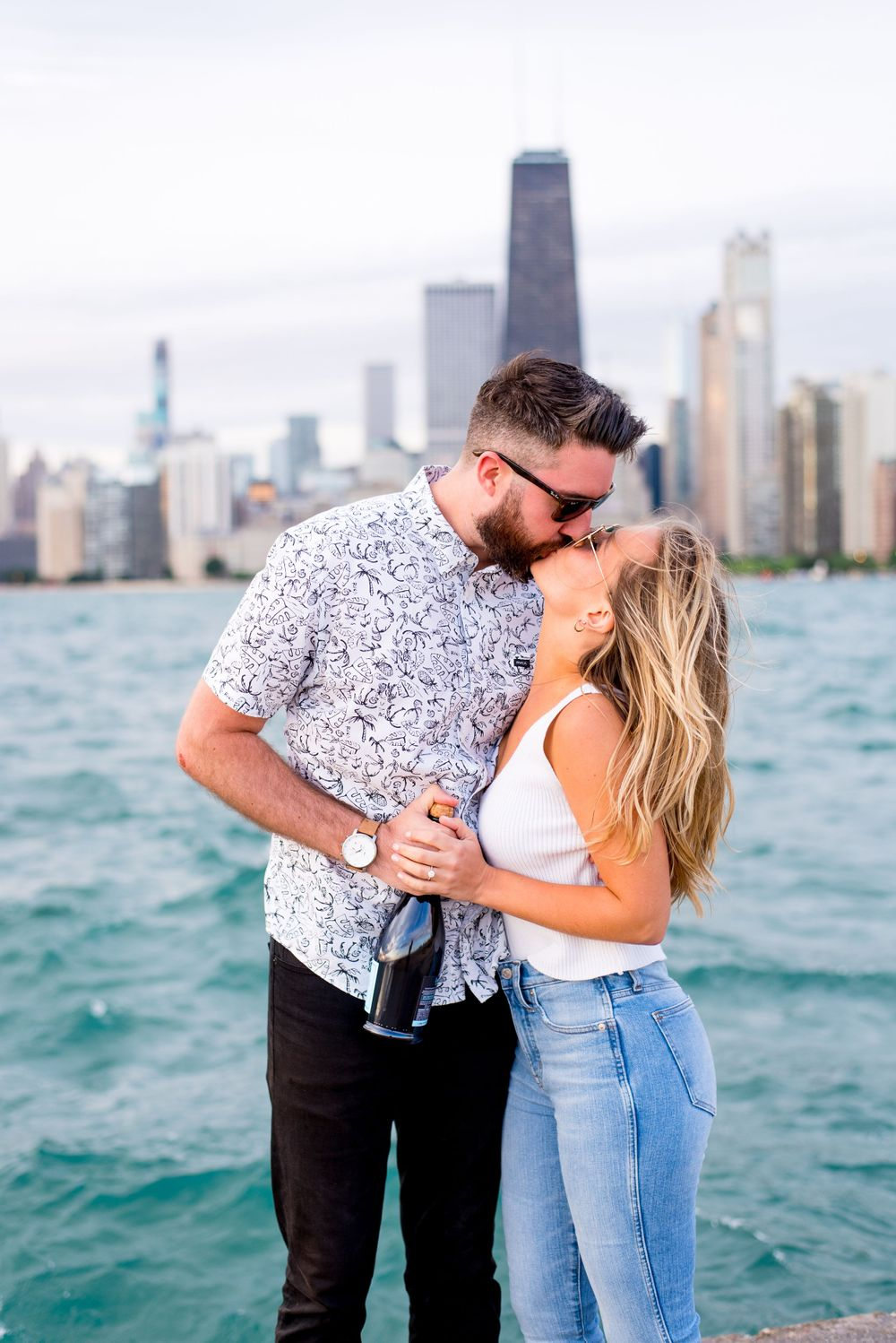 blonde woman and brunette man in sunglasses holding a bottle of champagne and kissing at North Avenue Beach Chicago