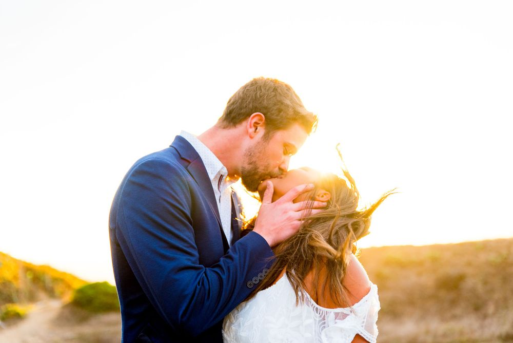 man in navy suit kissing and holding face of woman in white dress while her hair blows in the wind at sunset in Bay Area
