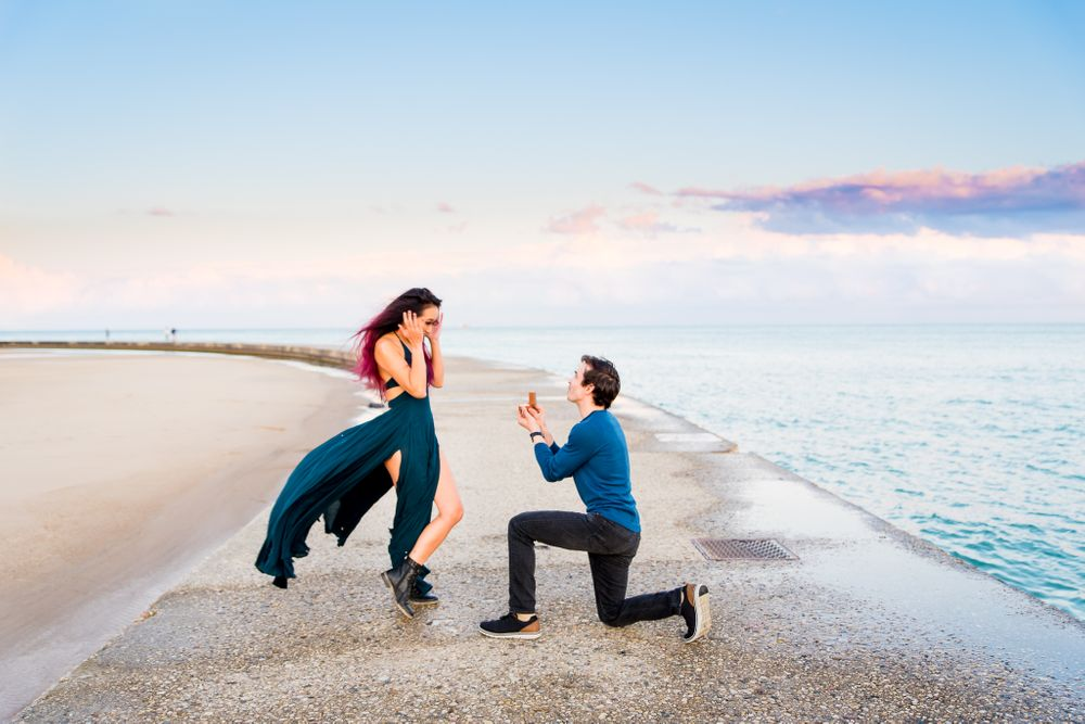 man on one knee proposing to woman in teal dress blowing in the wind at North Avenue Beach Chicago