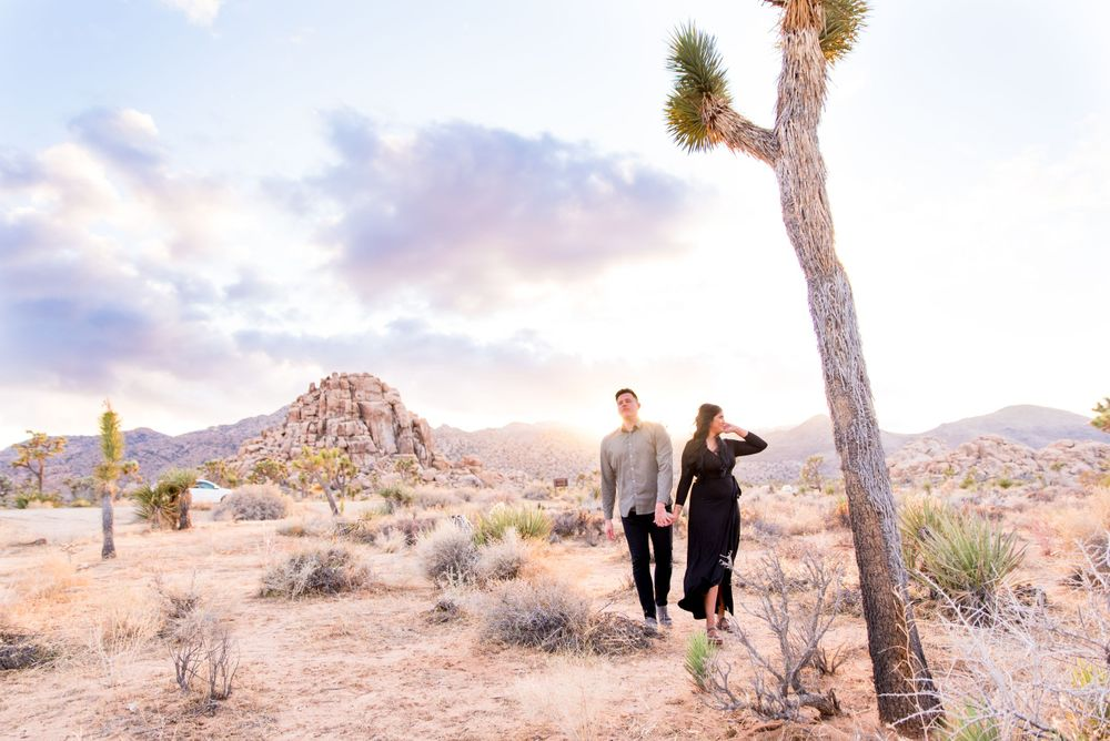 young engaged couple in black dress and gray shirt walking through Joshua Tree National Park holding hands