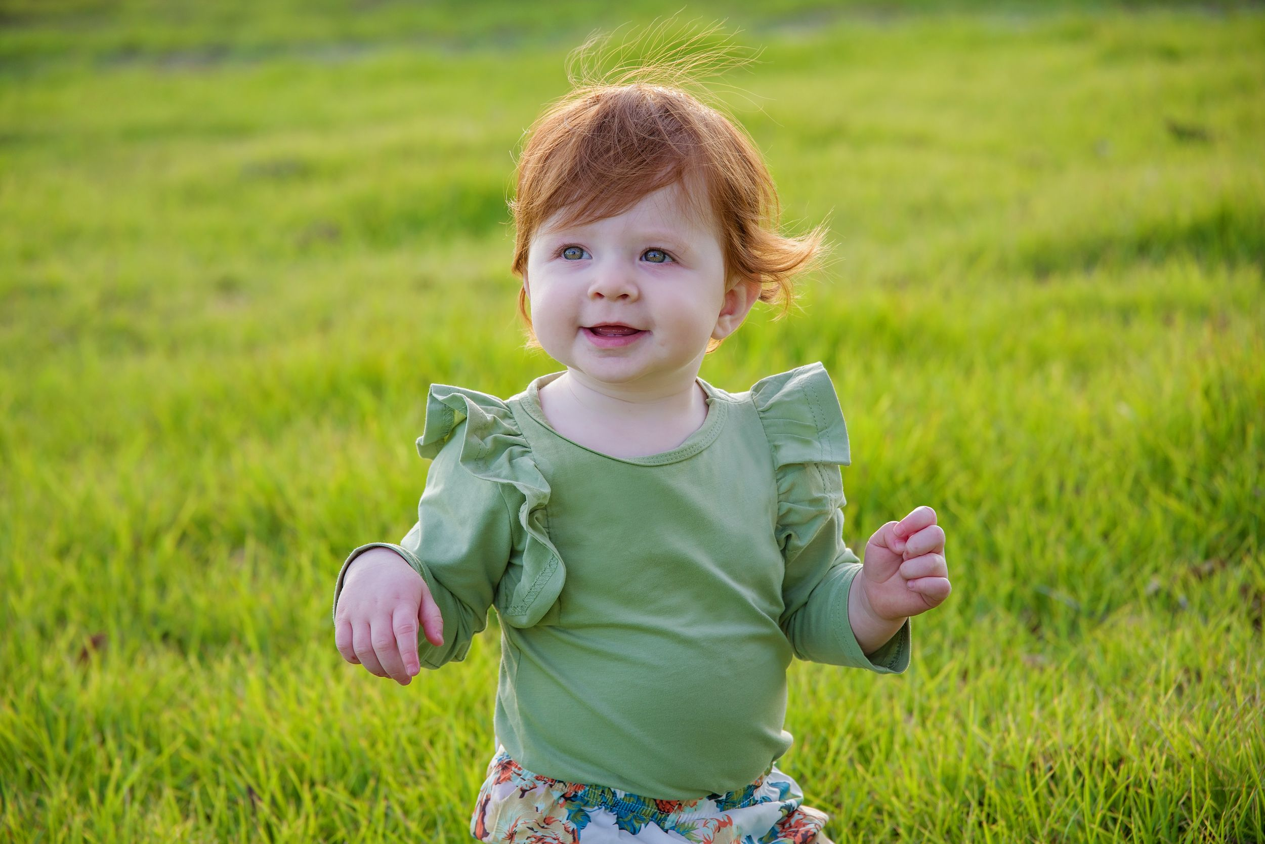 red headed baby sitting in greenery