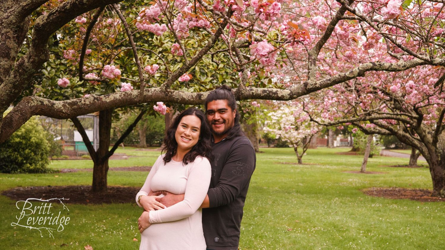 Pregnant lady with partner in front of flowering pink tree - Masterton NZ