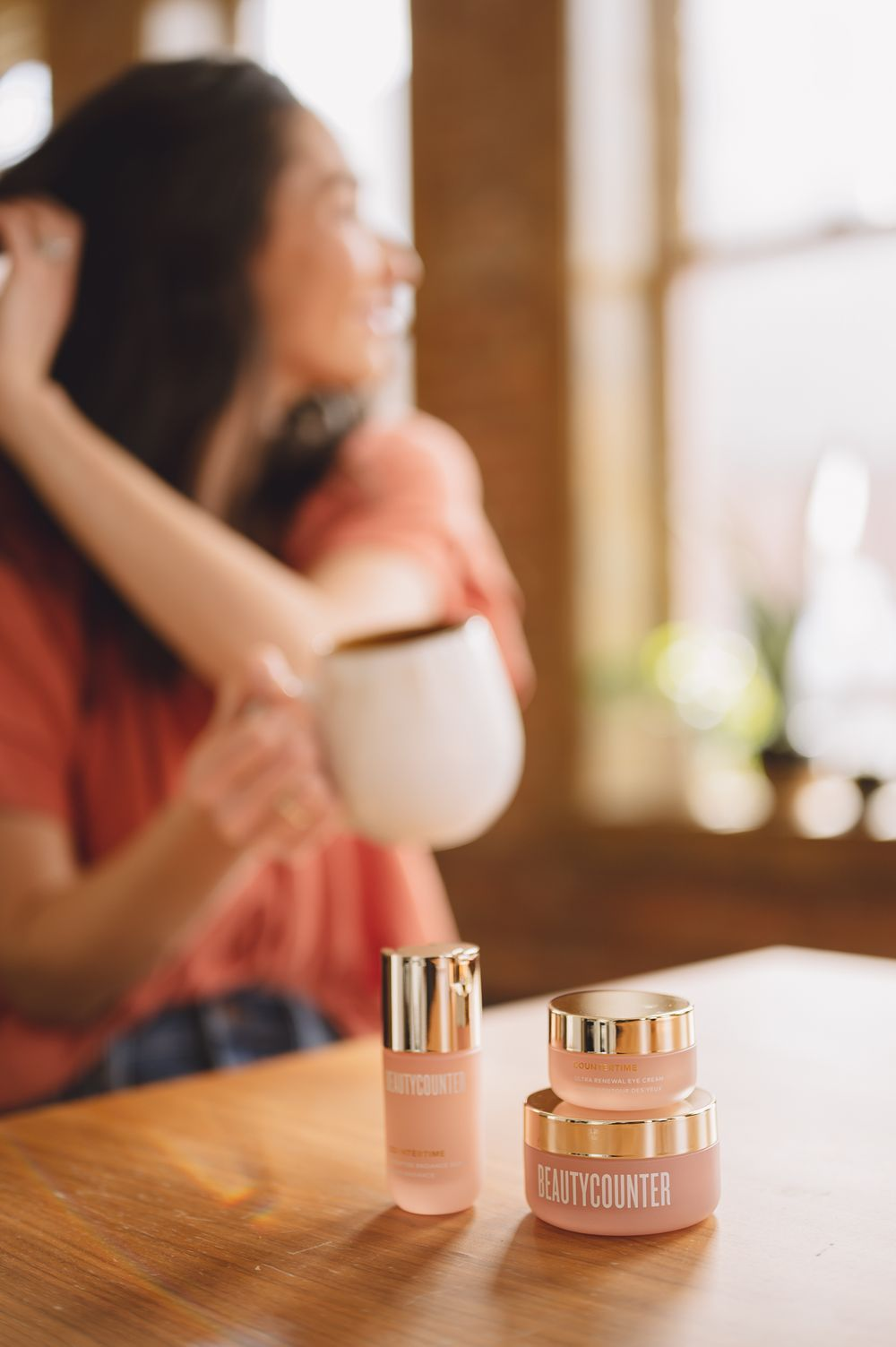 brand portrait by Tiffany Kelterer of Beautycounter product on table with blurred woman in background drinking coffee