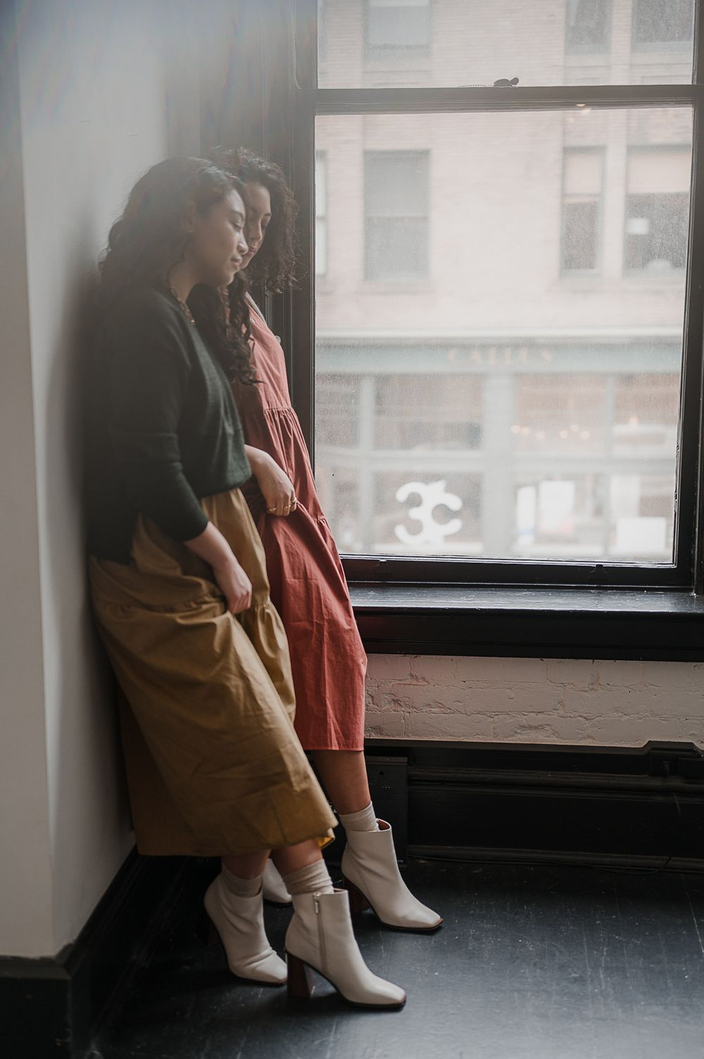 Brand campaign portrait by Tiffany Kelterer of two women leaning against a wall in Seattle fashion designers clothing