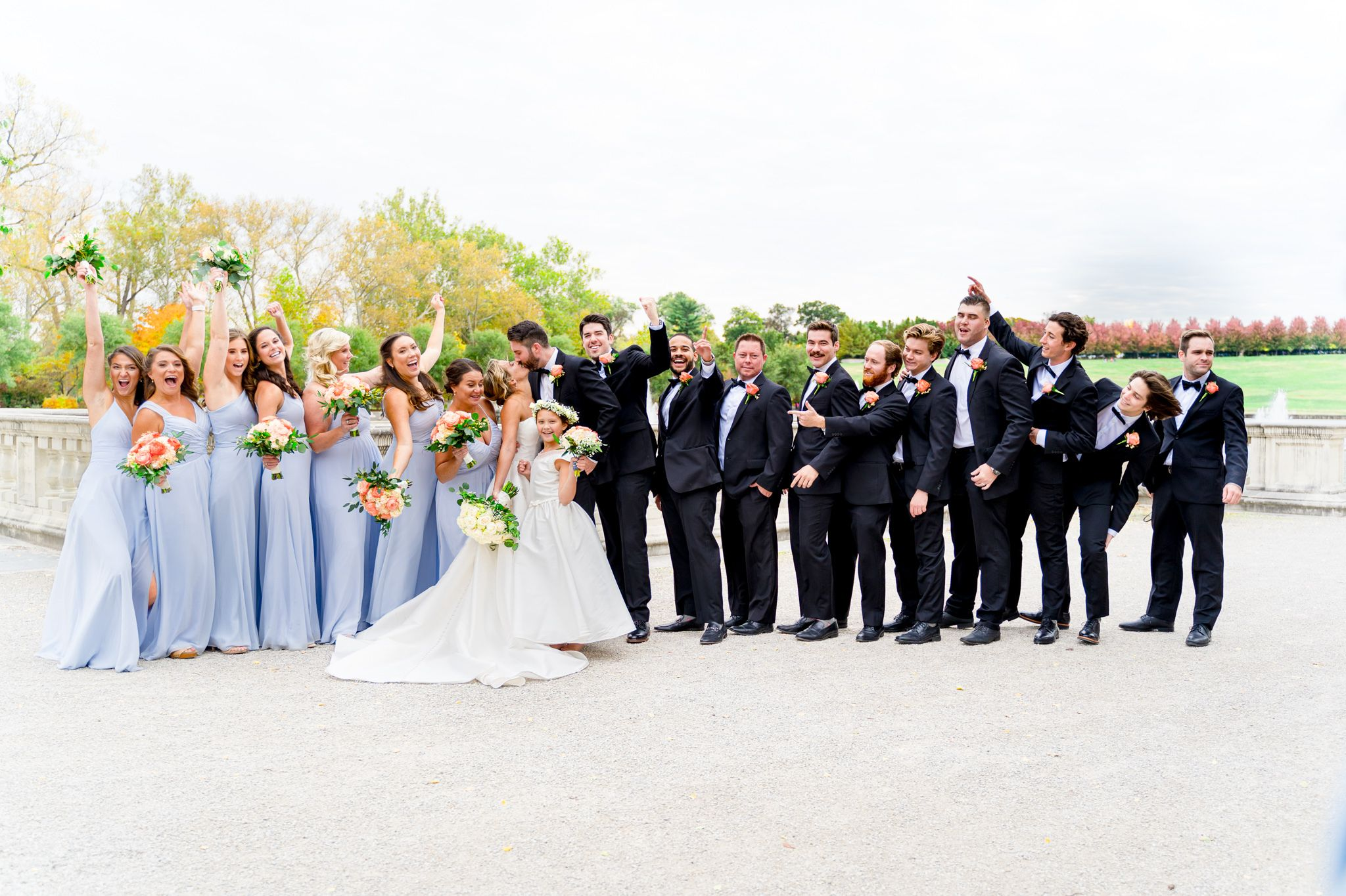 large wedding party in black suits and light blue dresses surround bride and groom at Forest Park in St. Louis