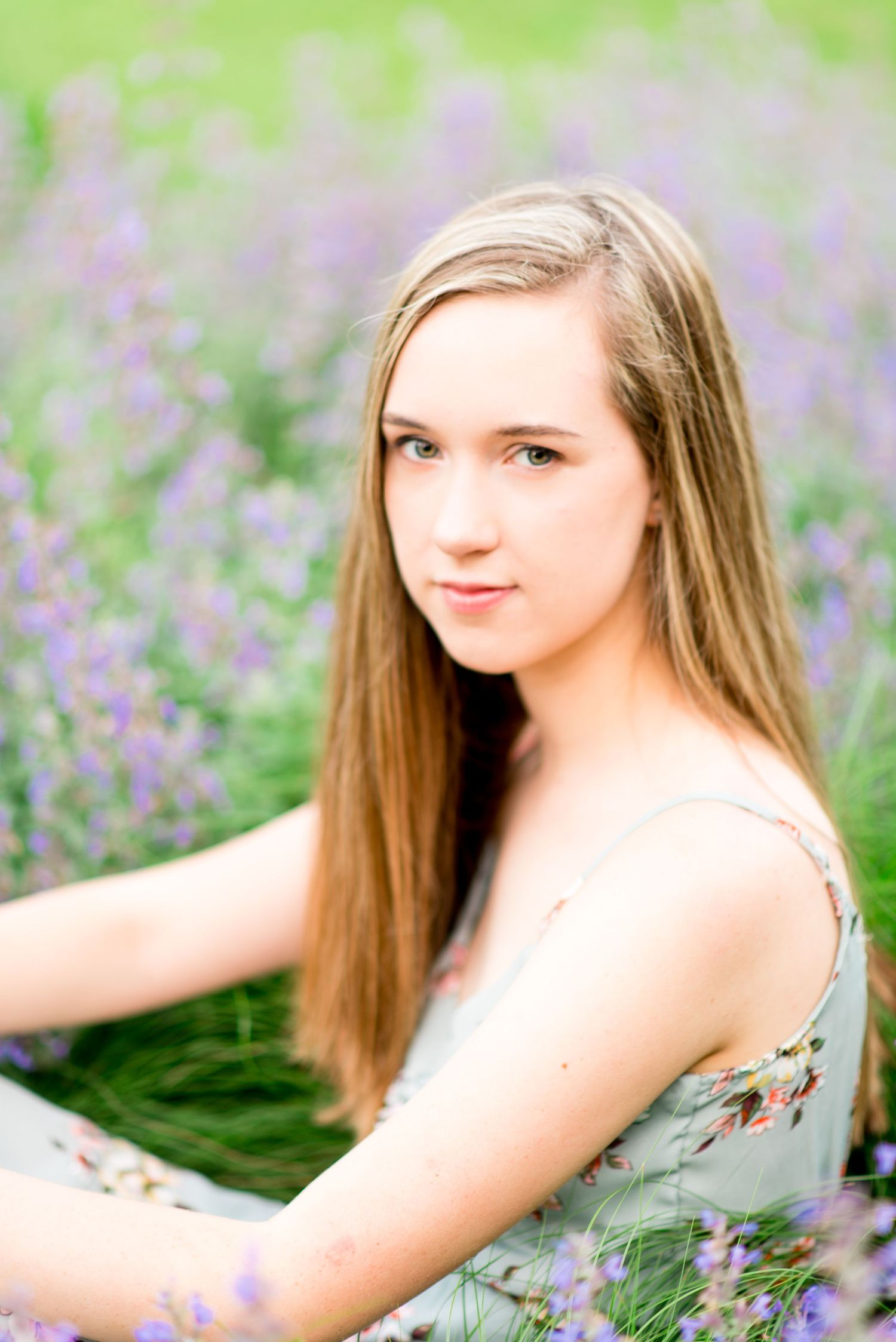 young woman with green eyes sits in a field of lavender in Chicago Lurie Garden for senior pictures