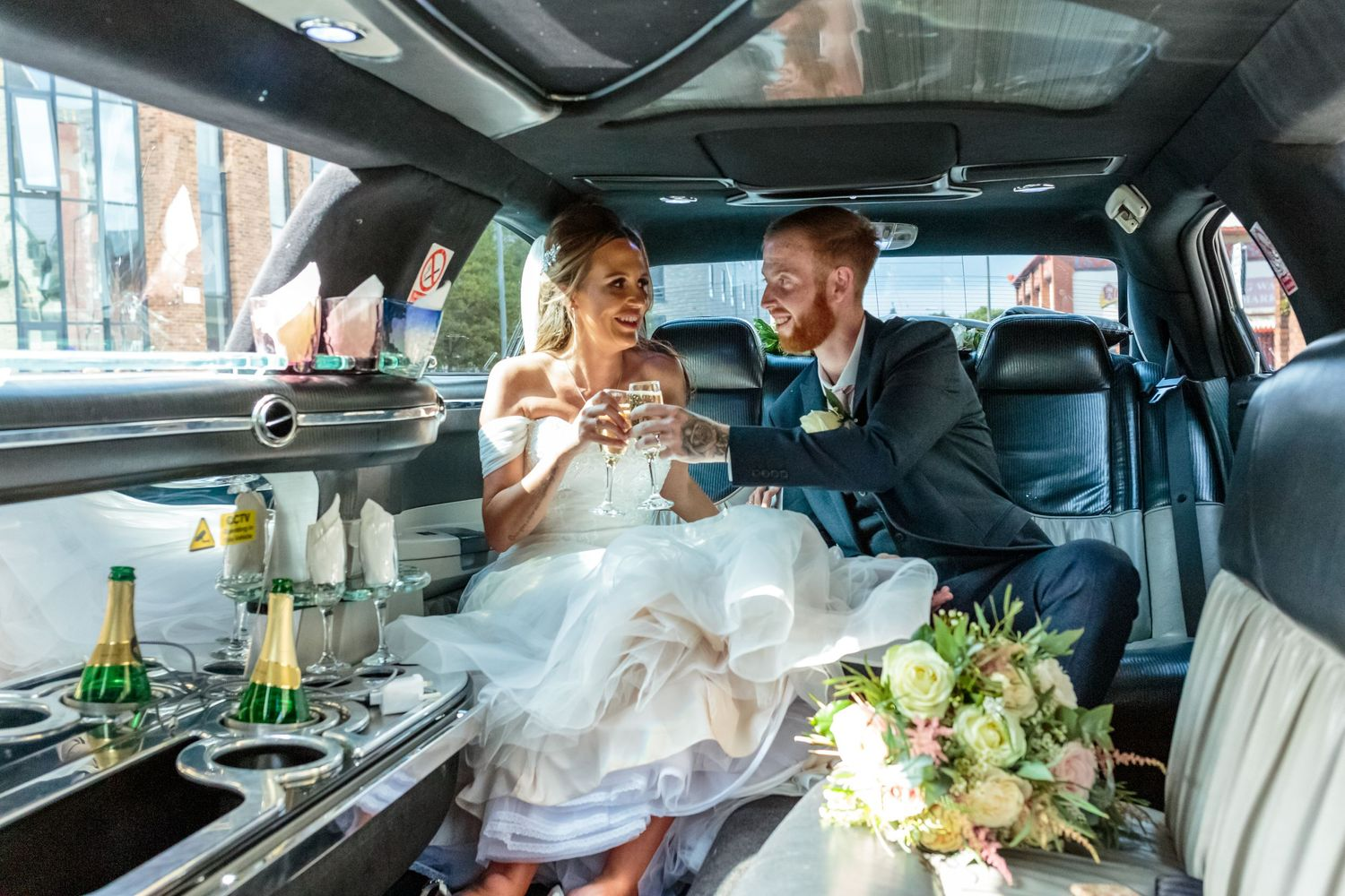 bride and groom clink champagne glasses sitting in the stretch limousine