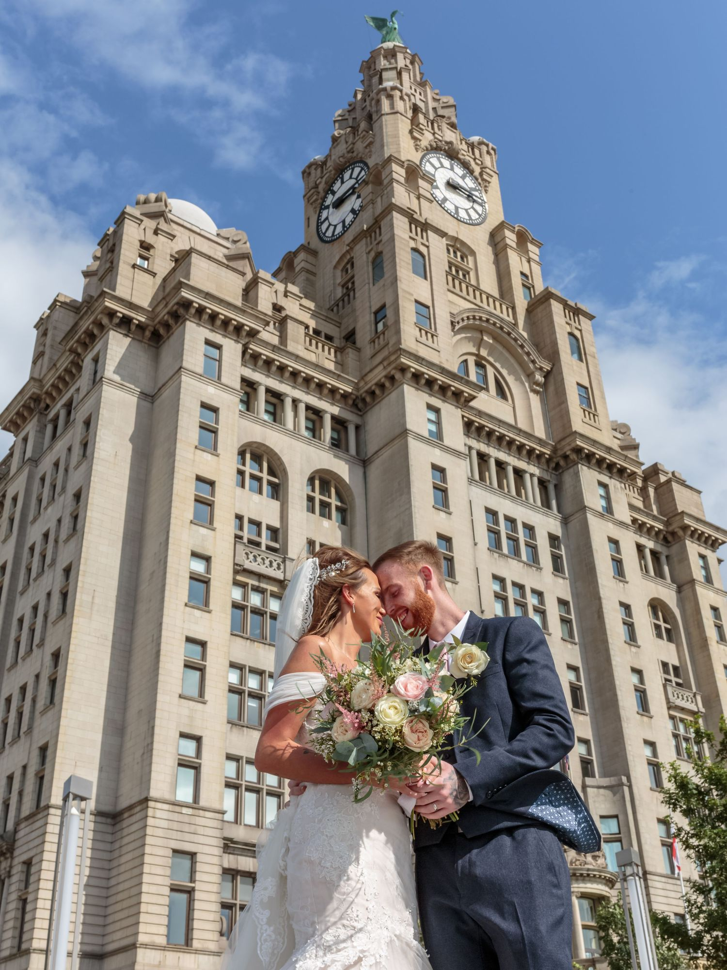 bride and groom kissing in front of the liver buildings on liverpools iconic water front