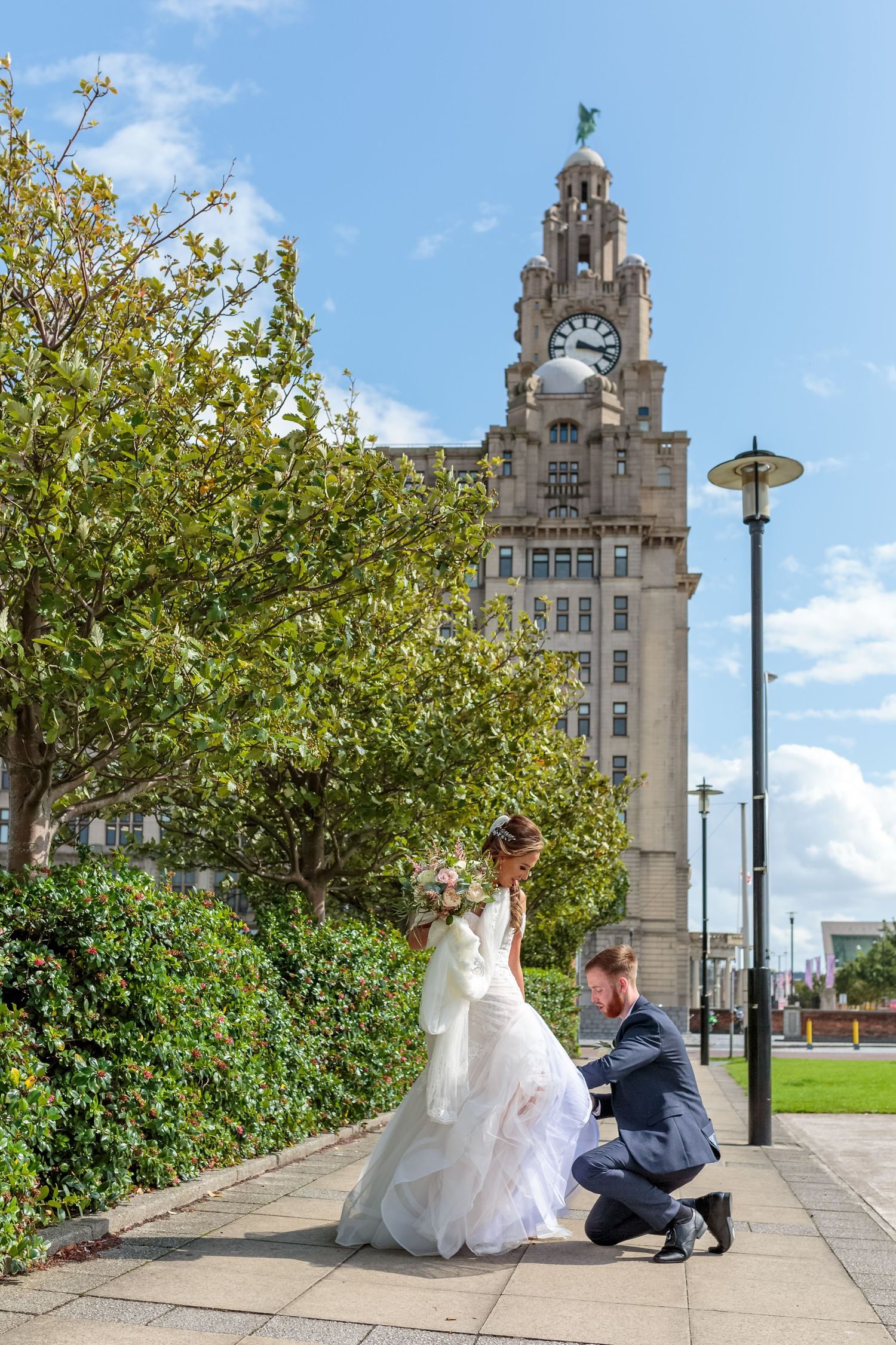groom stops to fasten the brides shoe on Liverpools famous water front with the liver buildings in the background