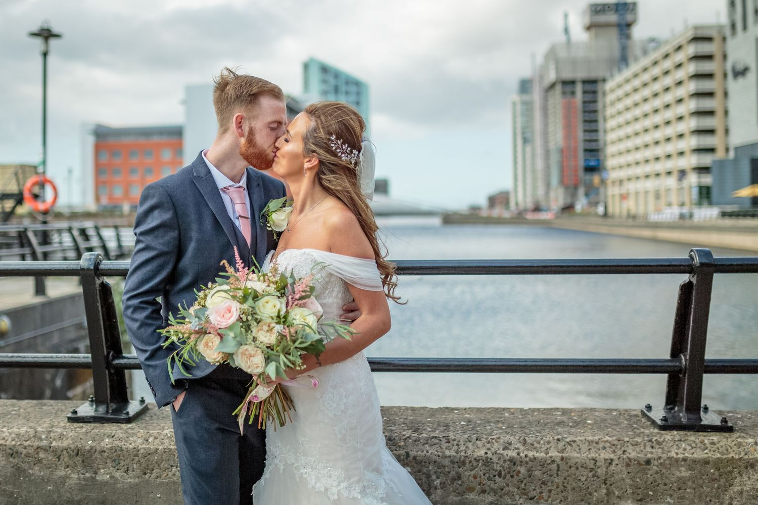 bride and groom kissing on Liverpools historic water front