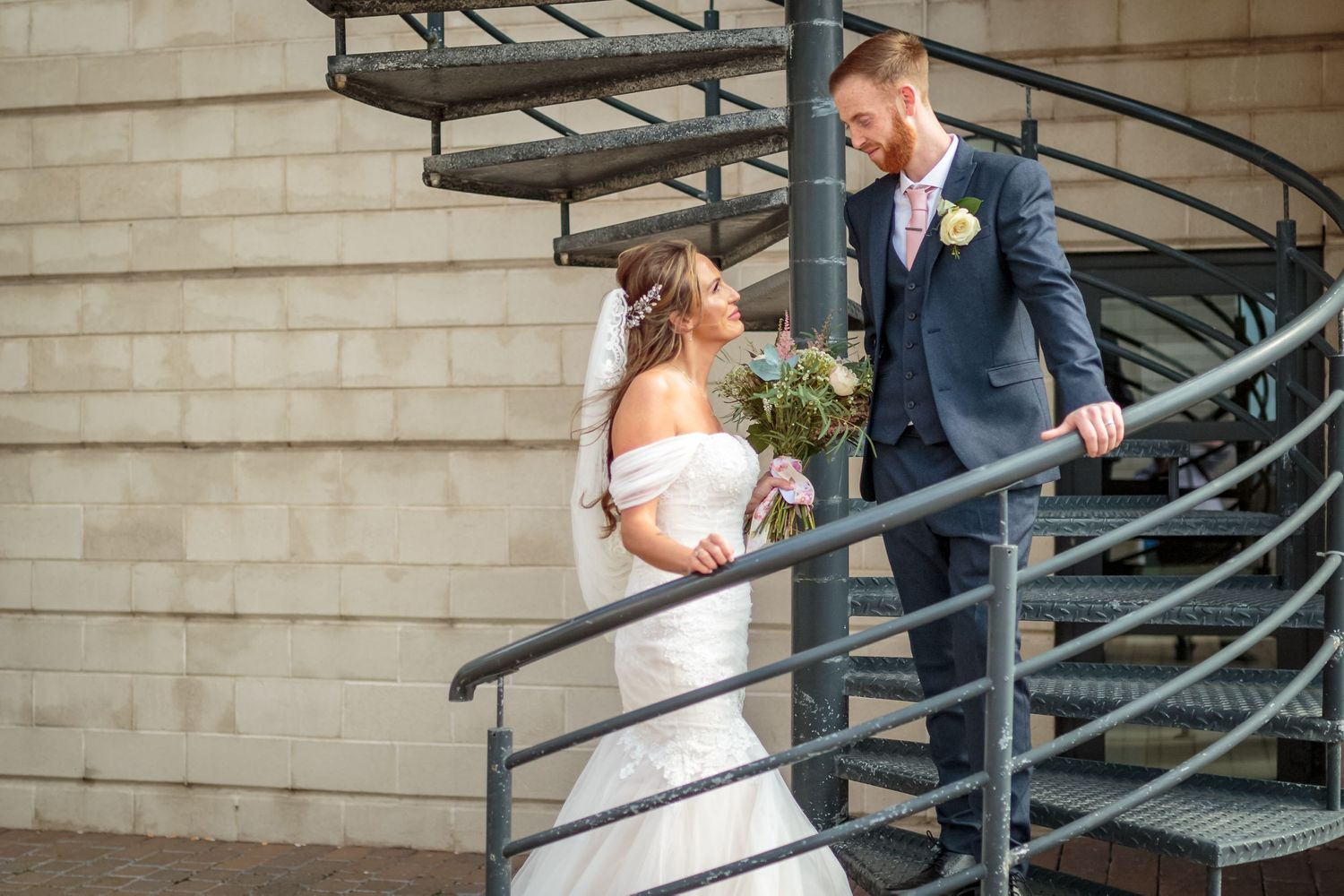 bride and groom pose on a spiral staircase on live pools waterfront