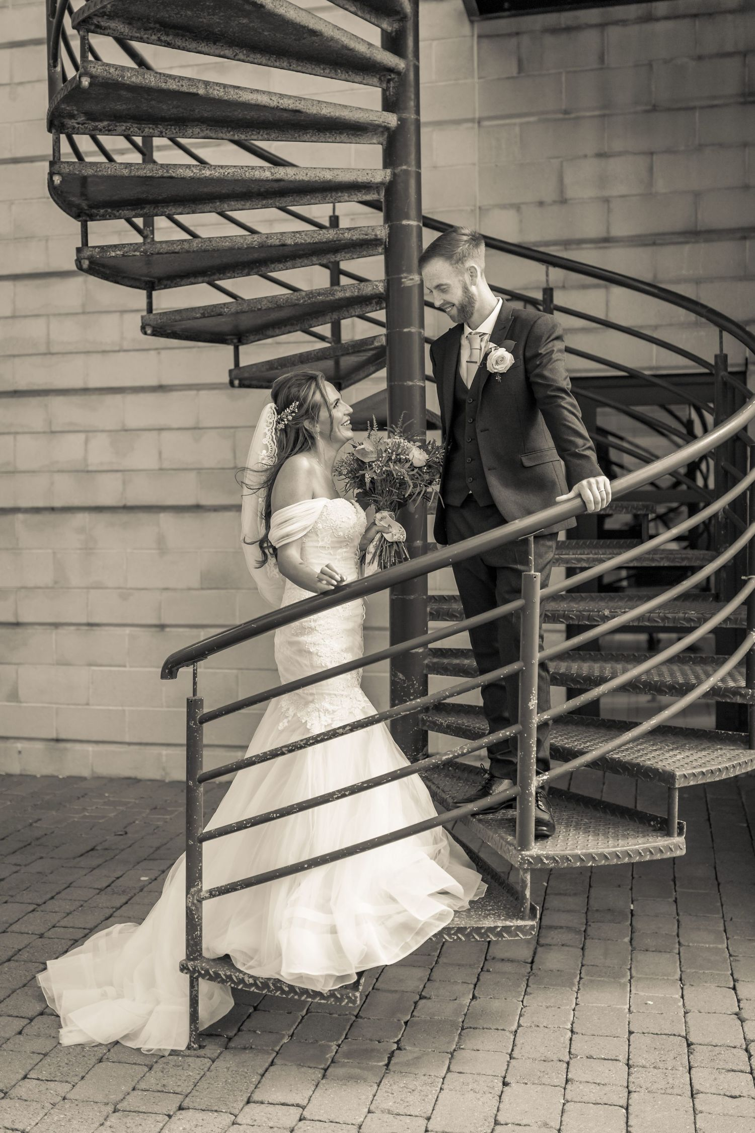 bride and groom looking at each other and smiling while posing on an industrial metal spiral straicase