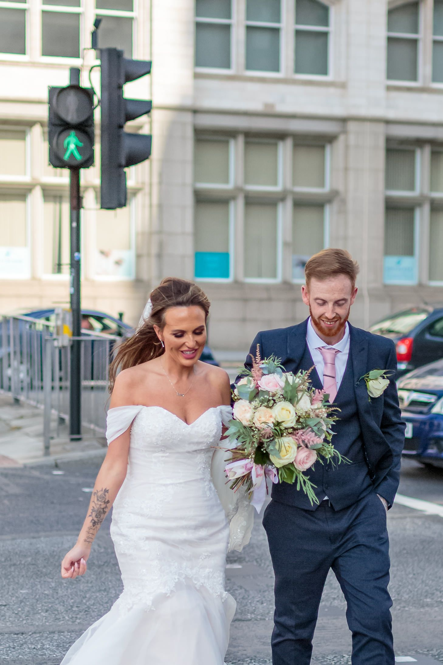 bride and groom smiling as they cross liverpools busy dock road