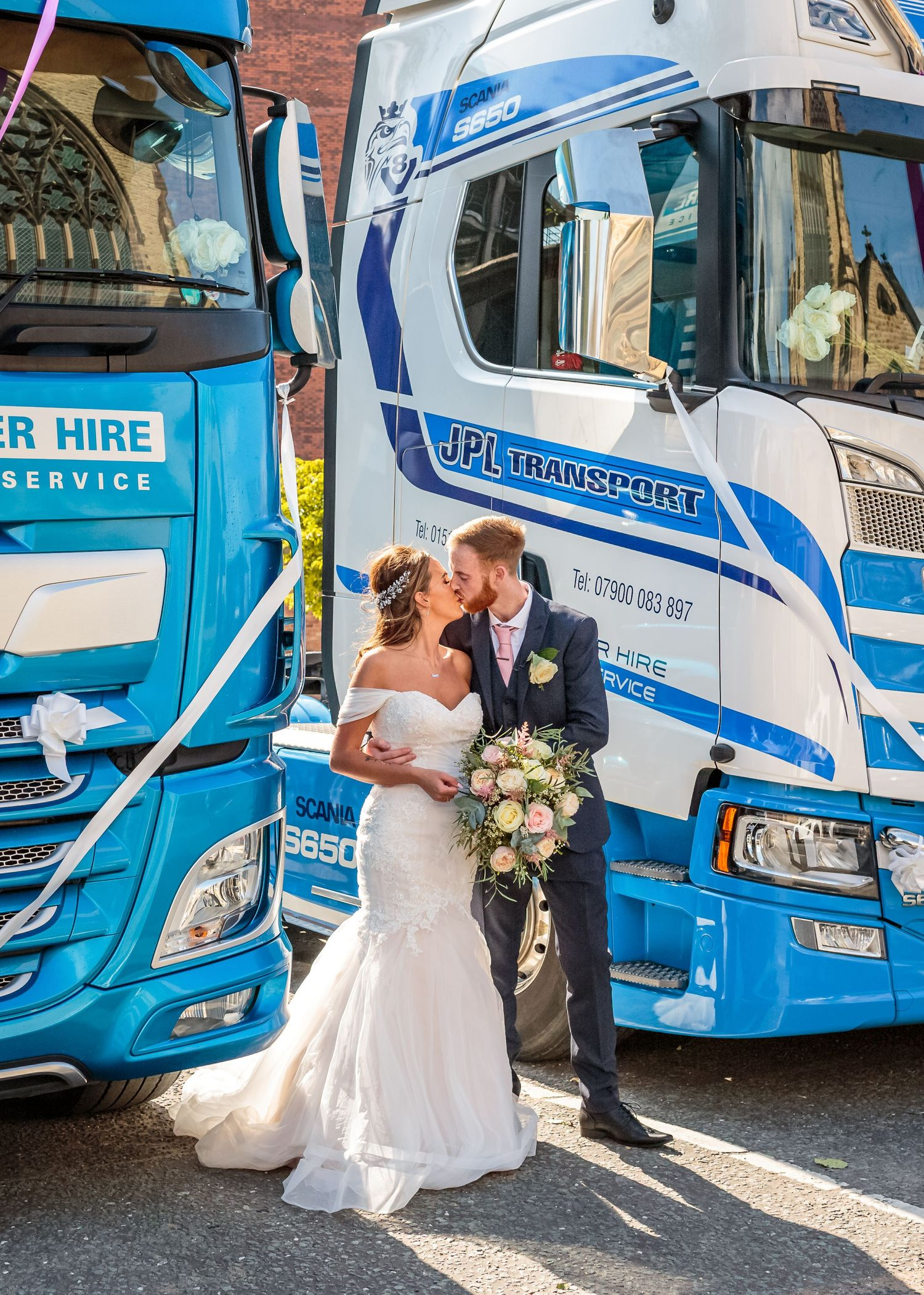 bride and groom kissing between to hgv cabs with wedding ribbons on the front