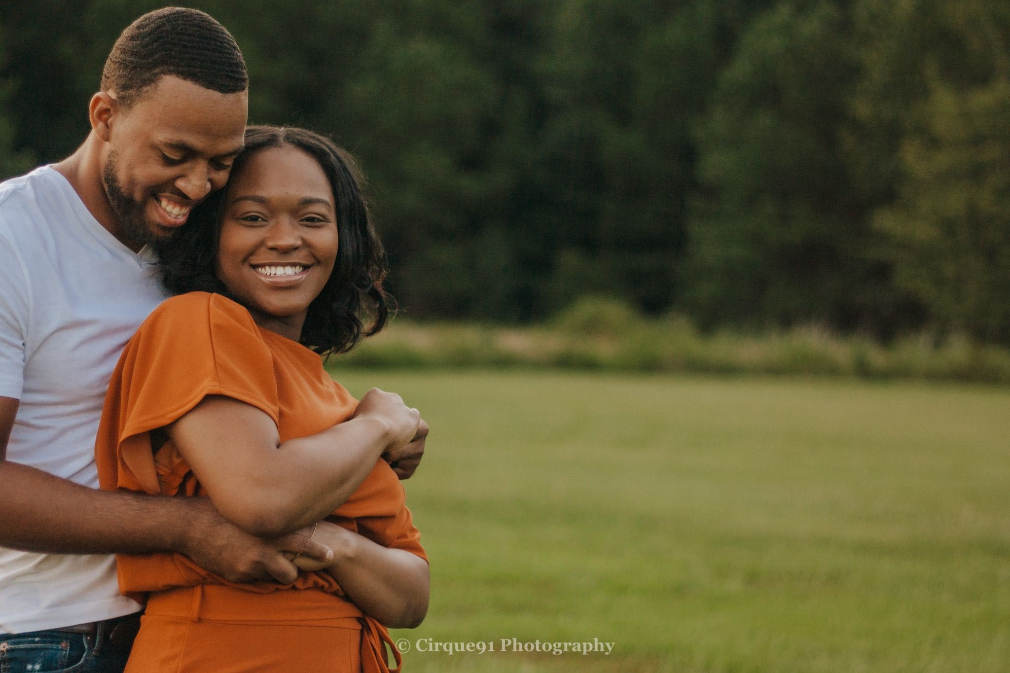 african american couple embracing and smiling at each other