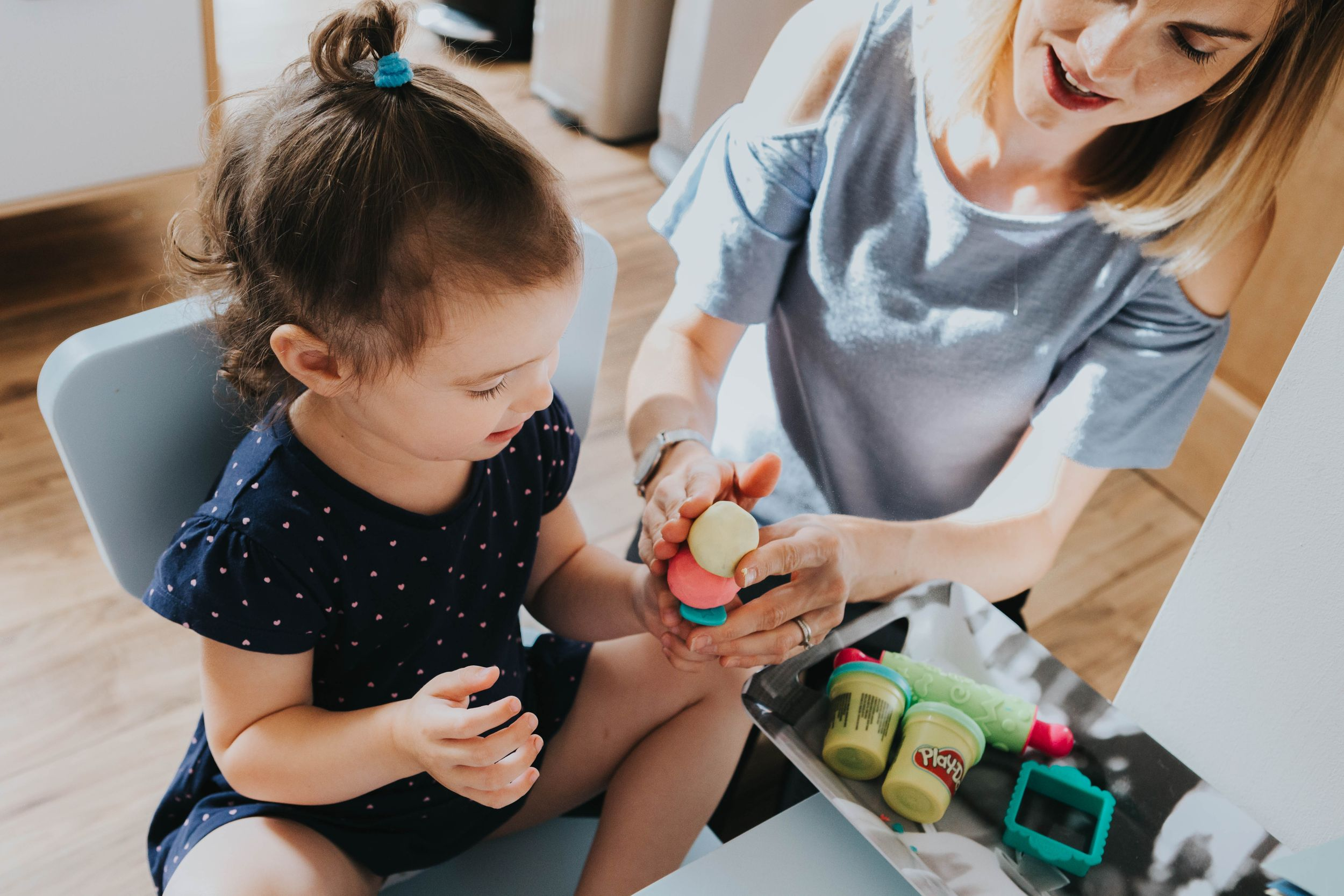 girl in navy dress playing play doh with mum