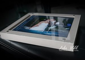 coeur d alene wedding book in a light beige box glass cover photographer luba wold couple kissing in a blue classic car