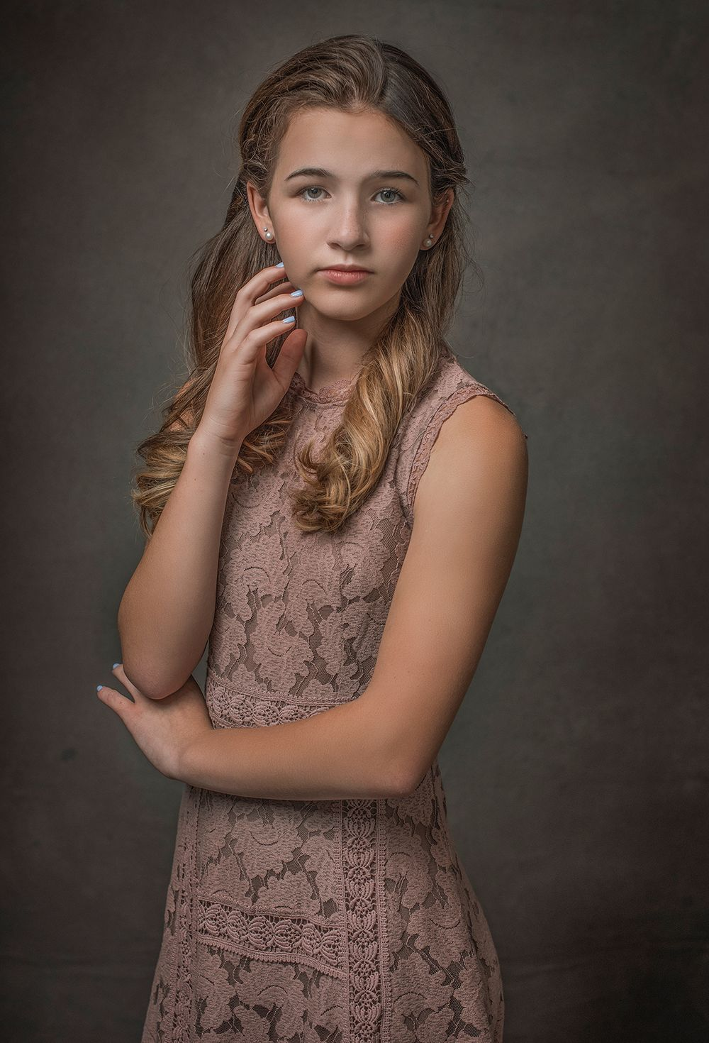 teen in pink dress hands crossed and on face