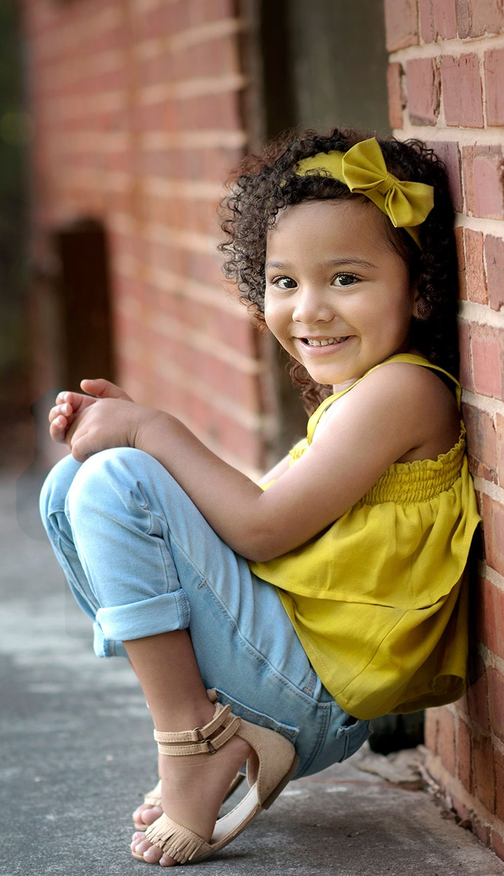 child leaning on brick wall in yellow shirt