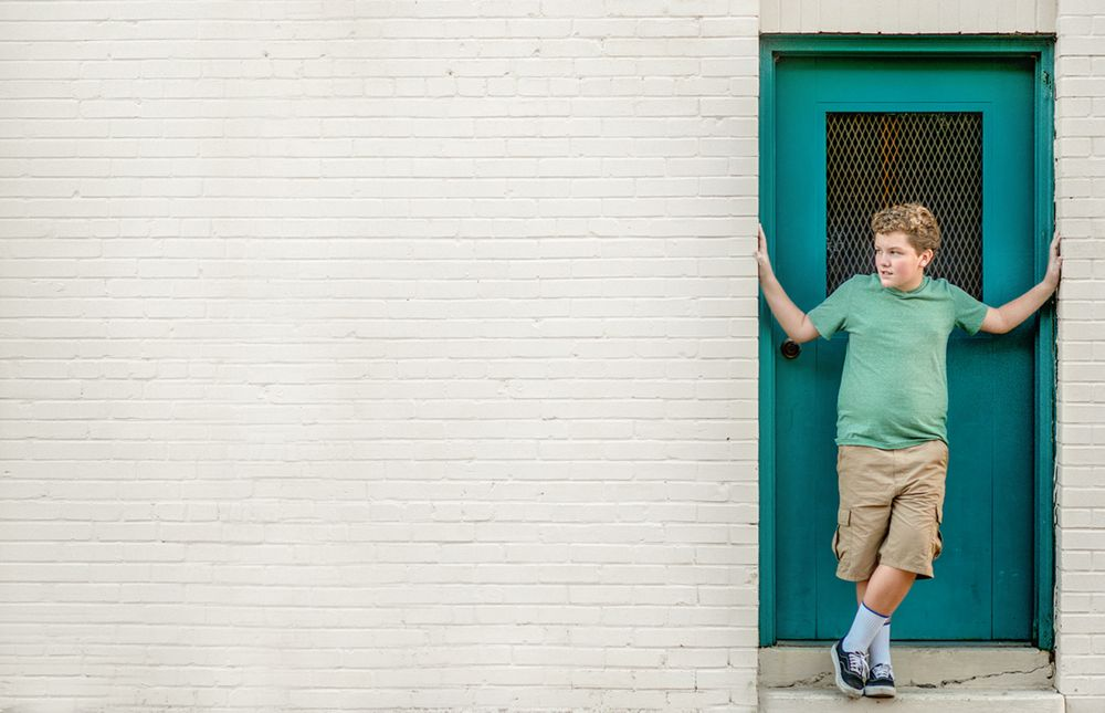 boy_on_white_wall_in_green_shirt