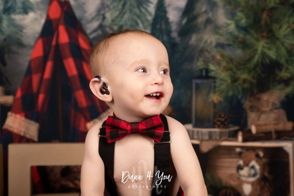 one year old photo shoot in colorado springs with hearing aid bowtie buffalo plaid
