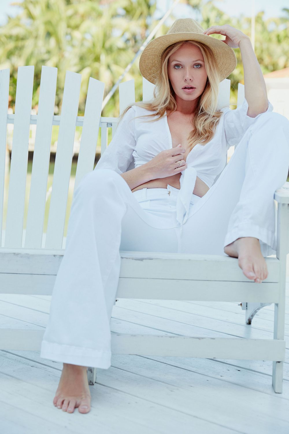 Model Carley Johnston wearing straw hat sitting in white rocking chair on a porch South Beach, Miami