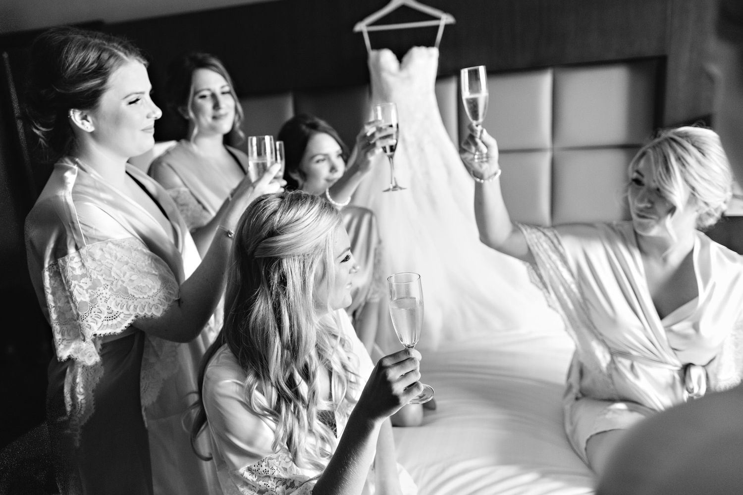 bride and bridsmaids clinking champagne glasses