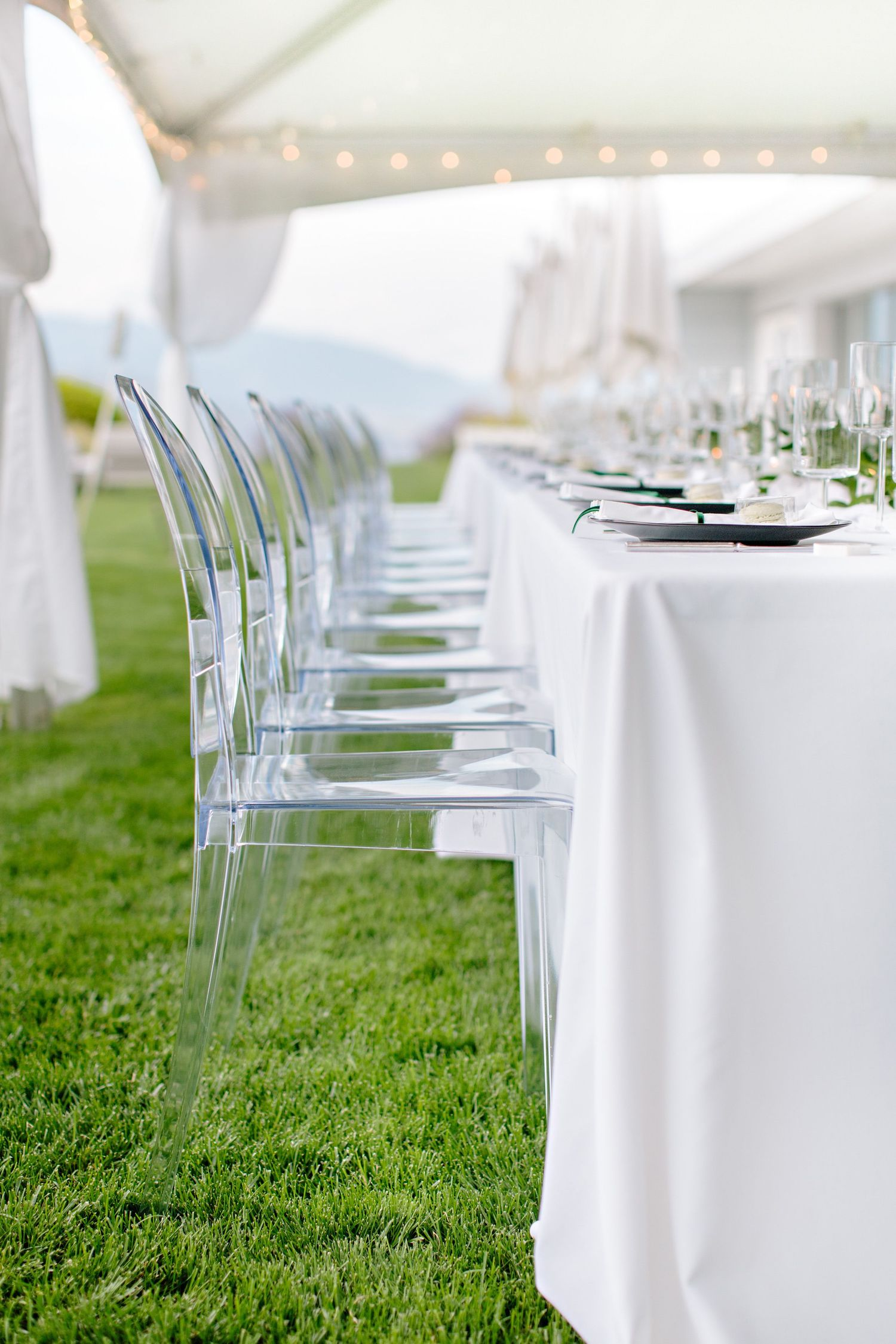 clear chairs and head table place setting